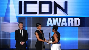 Rihanna accepting the award from her mum Monica as Bill Maher looks on