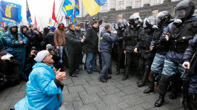 An elderly woman kneels before a line of riot police
