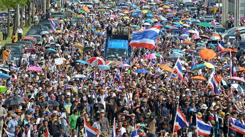Anti-government protesters wave national flags as they parade during a demonstration in Bangkok