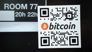 A sticker on a window indicates the acceptance of Bitcoins for payment