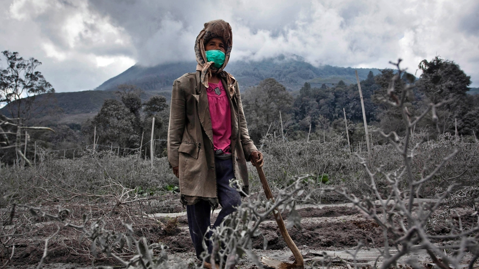 A woman stands in her field, which has been covered by ash from the eruption of Mount Sinabung in Indonesia