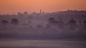 Mist lingers around trees on the Somerset Levels near Glastonbury