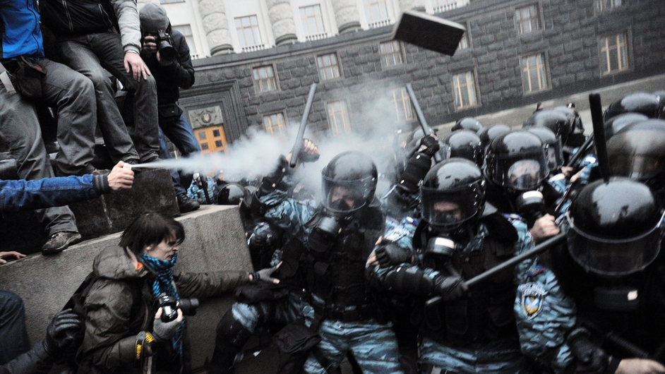 Protesters use tear gas and throw stones during clashes with riot police in Kiev