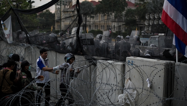 Anti-government protesters cut barb wire as they are coming close to pull one of the last concrete barricades outside the Government house during
