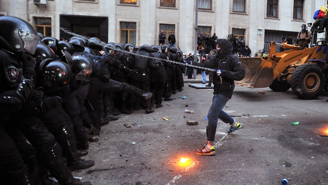 A protester with a chain clashes with police during the storming of the presidential office
