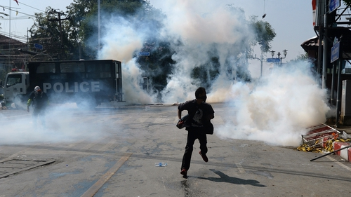 An anti-government protester runs as police fire tear gas shells at them outside Government house