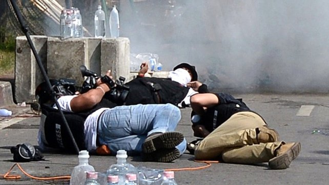 Media lie down on the ground as tear gas shells burst near them outside Government House