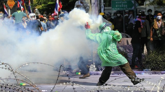 Protesters throw tear gas canisters back to police barricades during street battles near the Metropolitan Police Bureau