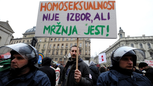 A protester holds a sign reading 'Homosexuality is not a choice, hate is a choice' next to riot policemen as Croatian gay rights activists protest in Zagreb