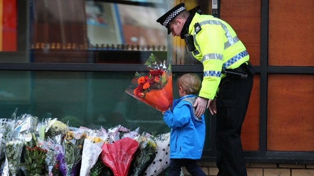 A policeman helps a small boy leave flowers at the scene