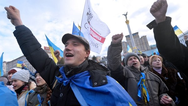 People shout slogans and wave flags of Ukraine and the European Union during a rally on Independence Square in Kiev
