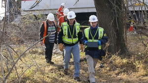 NTSB investigators carry an event recorder from the derailed commuter train in New York