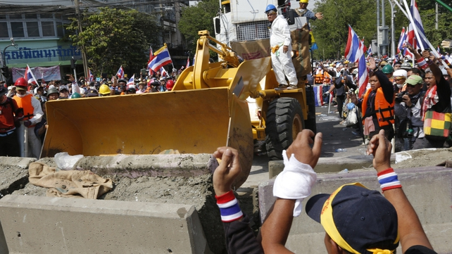 Protesters used a bulldozer to break down barriers outside Government House