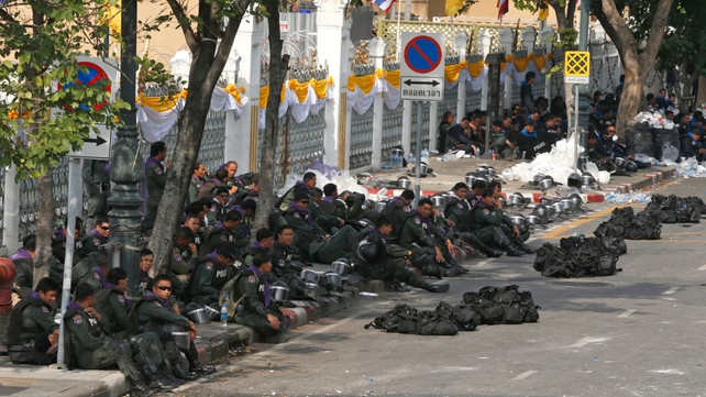 Police and army personnel rest after they were ordered to allow protesters into the state agencies