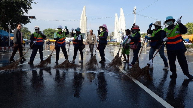 Street cleaners on the streets of Bangkok after protests dispersed