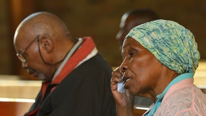 A woman wipes tears away during a prayer service for Nelson Mandela