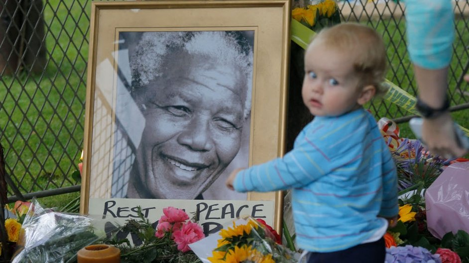 A little girl stands among the tributes placed outside Nelson Mandela's house in Johannesburg