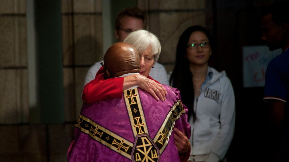 Archbishop Emeritus Desmond Tutu is hugged by a woman during a service in St George's Cathedral after the announcement of Mr Mandela's death