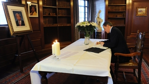 British Prime Minister David Cameron signs the book of condolence at the South African Embassy in central London