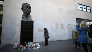 People look at floral tributes placed on a sculpture of Nelson Mandela in London