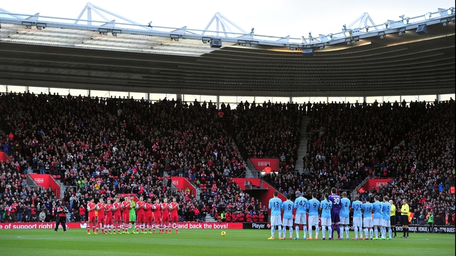 Teams and fans observe a minute of applause in memory of Nelson Mandela before kick-off