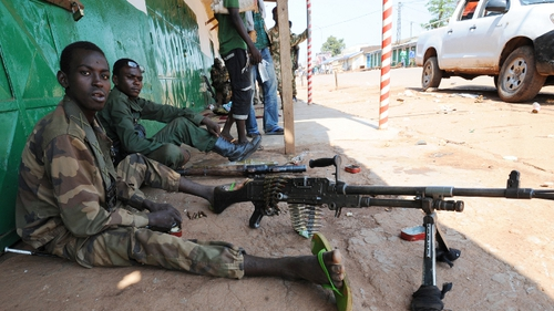 Ex-Seleka rebel ebels sits in the shade as they stand guard at a shut down market in Bangui