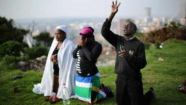 People worship on a hill overlooking Johannesburg as they remember and mourn Nelson Mandela