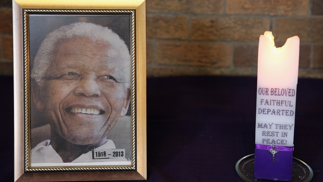 A candle burns next to a picture of the late Nelson Mandela during a Sunday service on a national day of prayer