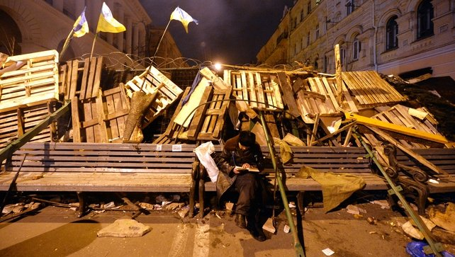 A protester reads a book as he guards one of the barricades on  Independence Square overnight