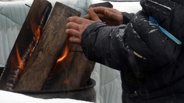 A man warms his hands as protesters defy freezing temperatures to maintain their presence in Independence Square