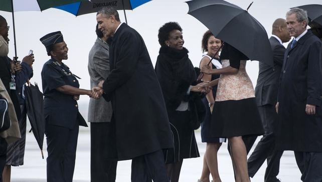 Barack Obama is greeted while arriving with First Lady Michelle Obama, former US president George W Bush and others at Waterkloof Air Base