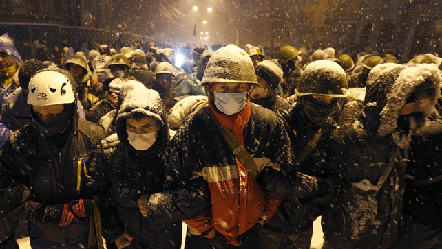 Protesters face riot police near the Presidential office building where thousands of demonstrators continued to demand the Ukrainian government's resignation