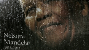 Rain falls on a poster of Nelson Mandela sitting in the window of a bus outside of Ellis Park