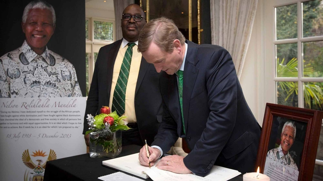 Taoiseach Enda Kenny signs a book of condolence for Mr Mandela at the South African ambassador's residence