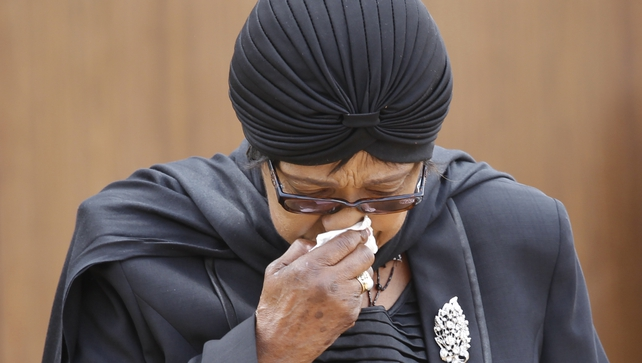 Winnie Mandela wipes away tears after viewing his coffin