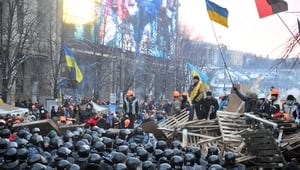 Riot policemen stand in front of a barricade held by protesters who defiantly refused to leave Independence Square