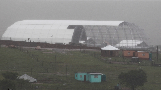 A giant dome under construction is seen through heavy rain in the home of Nelson Mandela in his ancestral village of Qunu ahead of his funeral