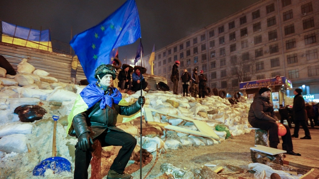 A man holds an EU flag in front of a barricade in central Kiev