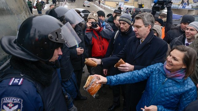US Assistant secretary of State for European and Eurasian Affairs Victoria Nuland (2-R) distributes cakes to riot police