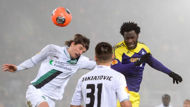 Swansea's Wilfried Bony heads clear from St Gallen's Daniele Russo and his teammate Dejan Janjatovic
