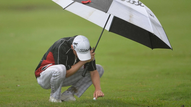 Michael Hoey attempts to remove his ball from the waterlogged turf in Durban