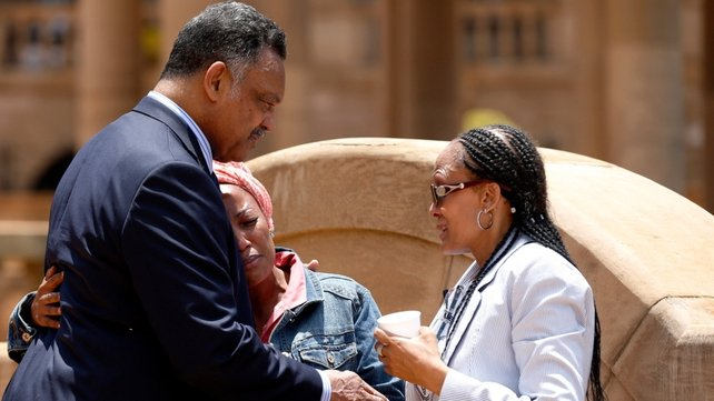 Rights campaigner Rev Jesse Jackson comforts a woman at Union Buildings