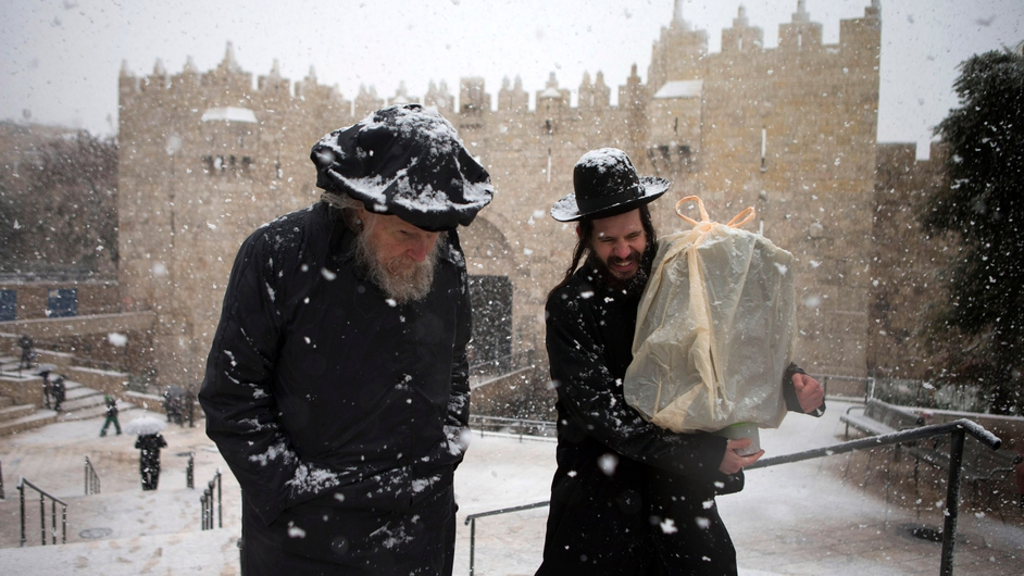 Two men make their way through the snow past the Damascus gate Jerusalem's old city