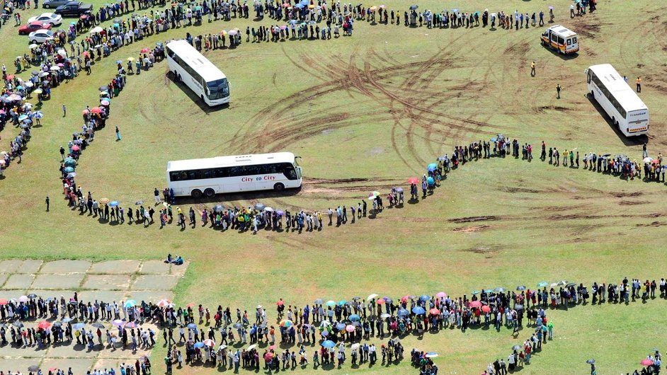 People standing in line as they queue to get on buses to view the coffin of Nelson Mandela during the lying in state in Pretoria