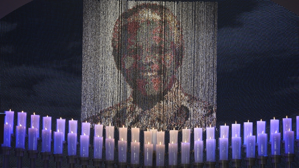 Candles are lit under a portrait of Neslon Mandela before the funeral ceremony of South African former president Nelson Mandela in Qunu