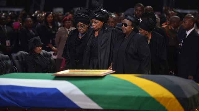 The ex-wife of Nelson Mandela, Winnie Mandela Madikizela (L), and the widow of Nelson Mandela, Graca Machel (C), stand by the coffin