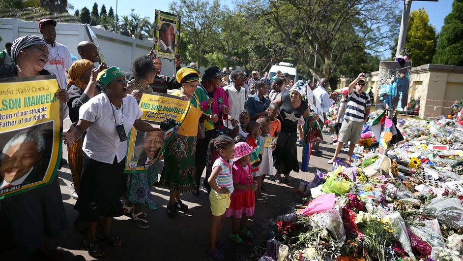 Crowds gather outside the home of Nelson Mandela in Johannesburg as he is laid to rest in his native village of Qunu