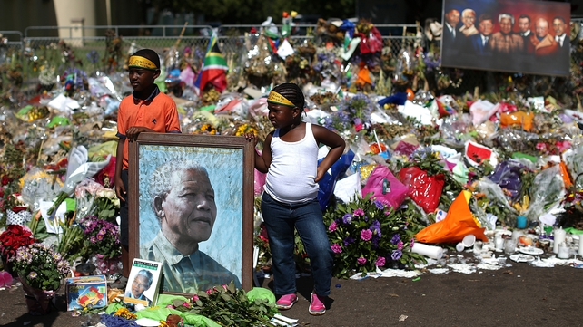 Children stand at a shrine outside Nelson Mandela's home in Johannesburg