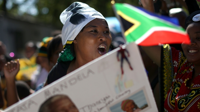 A woman sings outside Nelson Mandela's home in Johannesburg