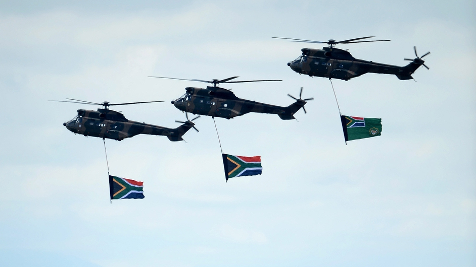 South African military helicopters fly over the burial site